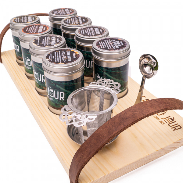 Presentation tea board with cans of tea, tea spoon and tea filter